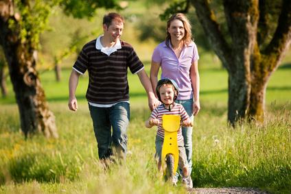 Spaziergang der Familie mit Kind und Laufrad