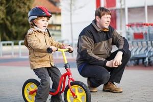 Kind auf Laufrad mit sicherem Schutzhelm