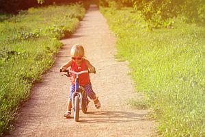 Abbildung: Mädchen ist unterwegs auf einem Laufrad