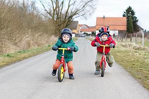 Abbildungen: Zwei Jungen auf ihren Laufrädern